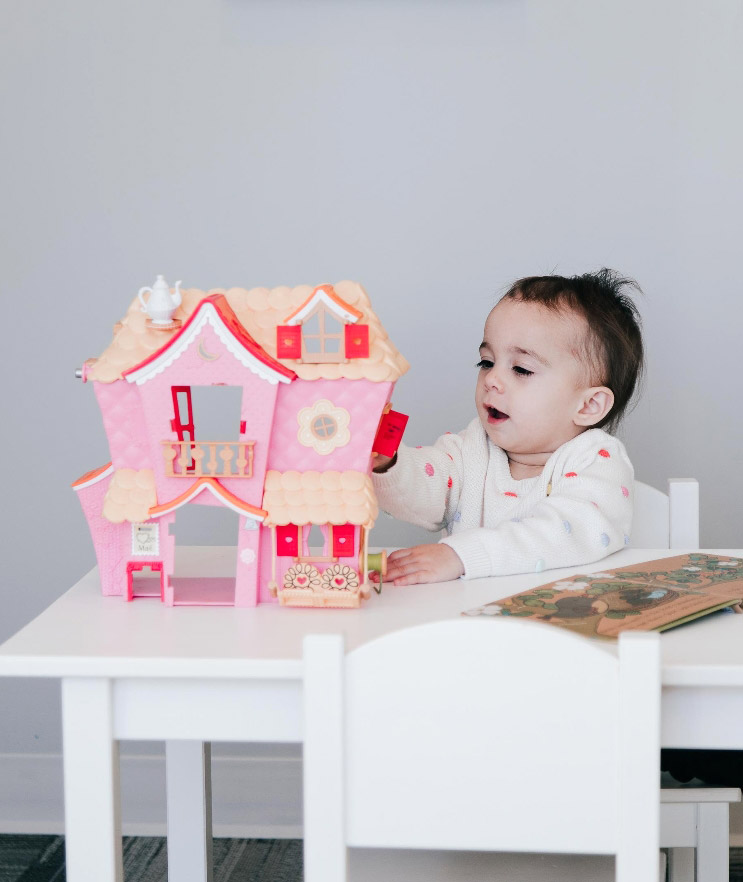 Child playing with a dollhouse